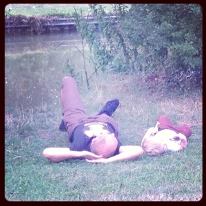 father and son laying down by the canal